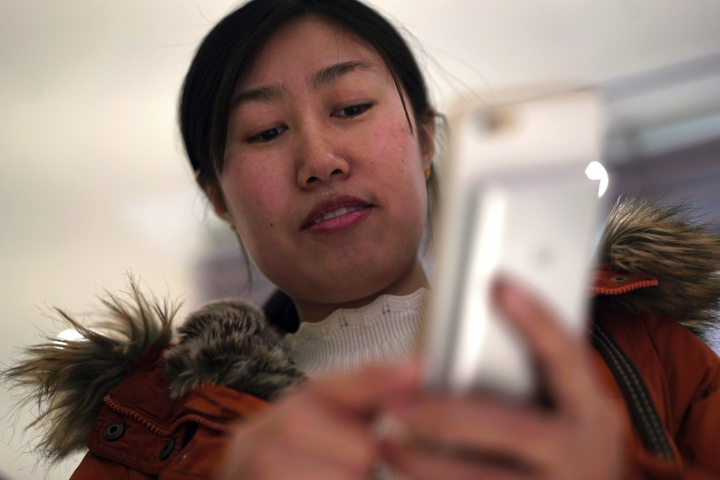 "In this Feb. 7, 2018 photo, Jia Weiwei demonstrates how to play the Japanese mobile game Travel Frog on her smartphone in Beijing. The Japanese mobile game Travel Frog has attracted a massive following in China by speaking to a desire for a more passive existence among harried youngsters that some have termed ""Buddhist style"" for its desired goal of Zen-like serenity. (AP Photo/Dake Kang)"