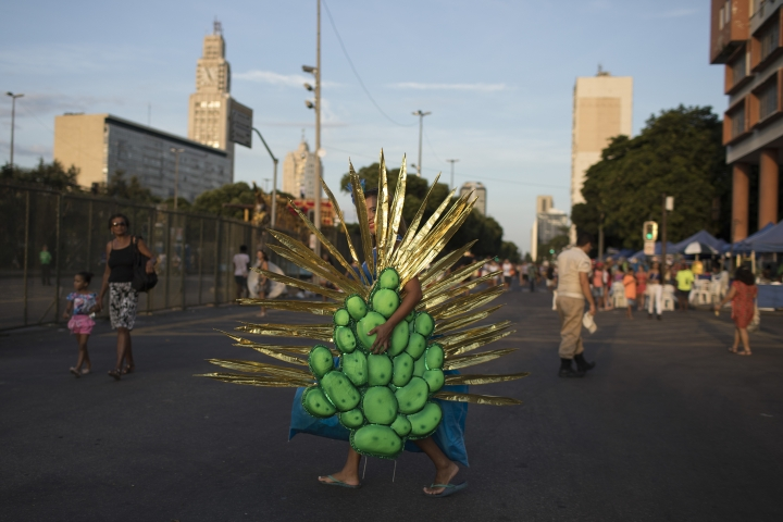 A woman carries her costume for Carnival celebrations to the Sambadrome in Rio de Janeiro, Brazil, Monday, Feb. 12, 2018. (AP Photo/Leo Correa)