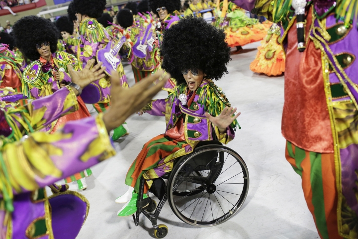 Performer from the Academicos do Grande Rio samba school parade on her wheel chair during Carnival celebrations at the Sambadrome in Rio de Janeiro, Brazil, Monday, Feb. 12, 2018. (AP Photo/Silvia Izquierdo)