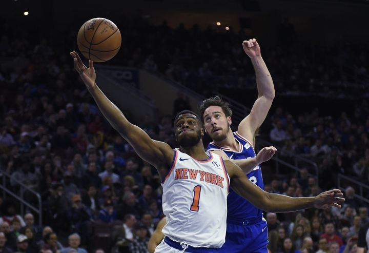 New York Knicks' Emmanuel Mudiay (1) and Philadelphia 76ers' T.J. McConnell (12) reach for loose ball in the first half of an NBA basketball game, Monday, Feb 12, 2018, in Philadelphia. (AP Photo/Michael Perez)