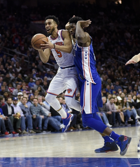 New York Knicks' Courtney Lee (5) draws a foul from Philadelphia 76ers' Joel Embiid (21) in the first half of an NBA basketball game, Monday, Feb 12, 2018, in Philadelphia. (AP Photo/Michael Perez)