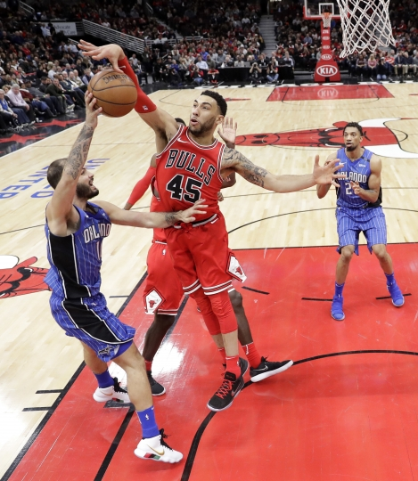 Chicago Bulls' Denzel Valentine (45) blocks a pass by Orlando Magic's Evan Fournier during the second half of an NBA basketball game Monday, Feb. 12, 2018, in Chicago. Bulls won 105-101. (AP Photo/Charles Rex Arbogast)