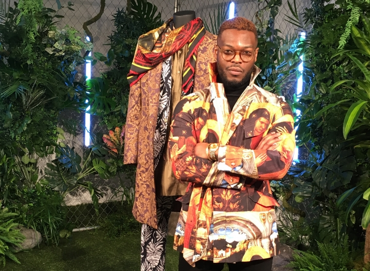 """Wale Oyejide, founder of the brand Ikire Jones, stands with his menswear design for a fashion collection inspired by the superhero film """"Black Panther,"""" Monday, Feb. 12, 2018, in New York. The designs will be auctioned to benefit the charity Save the Children. (AP Photo/Leanne Italie)"""