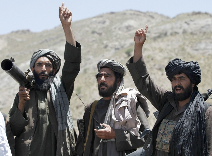 FILE - In this May 27, 2016 file photo, Taliban fighters react to a speech by their senior leader in the Shindand district of Herat province, Afghanistan. Despite US President Donald Trump's pronouncement that there would be no talks with the Taliban following a series of deadly attacks in Kabul, officials say talks continue, but neither side trusts the other and neither believes the other negotiates independently. (AP Photos/Allauddin Khan, File)