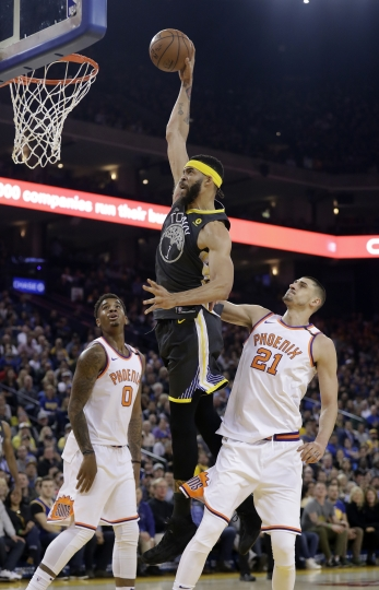 Golden State Warriors' JaVale McGee, center, dunks past Phoenix Suns' Marquese Chriss (0) and Alex Len (21) during the first half of an NBA basketball game Monday, Feb. 12, 2018, in Oakland, Calif. (AP Photo/Marcio Jose Sanchez)