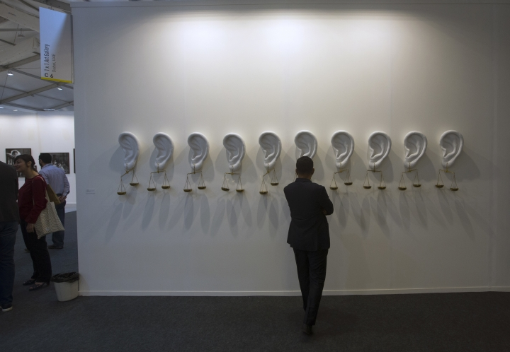 """In this Friday, Feb. 9, 2018, photo, a person looks at the Indian artist Sachin Bonde's creation """"Sounds Good"""" during India Art Fair in New Delhi, India. Human displacement, the suffering of refugees and the notion of identity dominated the 2018 India Art Fair, an important platform for contemporary artists that provides a carefully curated glimpse into the Asian art scene through the years. (AP Photo/Manish Swarup)"""