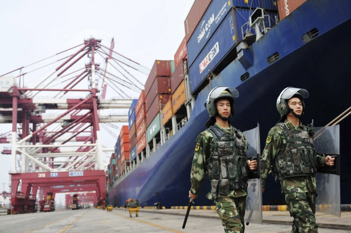 FILE - In this Sept. 8, 2016, file photo, paramilitary police patrol near a cargo ship at a port in Qingdao in eastern China's Shandong province. China imposed measures Tuesday, Feb. 13, 2018, against importers of a U.S. industrial chemical, requiring them to post deposits in preparation for possible anti-dumping duties amid rising trade tension with Washington. (Chinatopix via AP, File)