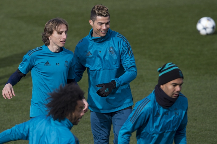 Real Madrid's Cristiano Ronaldo, center, smiles next to Luka Modric, left, during a training session in Madrid, Spain, Tuesday Feb. 13, 2018. Real Madrid will play Paris Saint Germain Wednesday in a Round of 16, 1st leg Champions League soccer match. (AP Photo/Paul White)