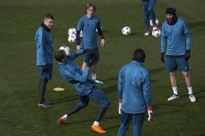 Real Madrid's Cristiano Ronaldo, left balances a ball on his shoulder during a training session in Madrid, Spain, Tuesday Feb. 13, 2018. Real Madrid will play Paris Saint Germain Wednesday in a Round of 16, 1st leg Champions League soccer match. (AP Photo/Paul White)