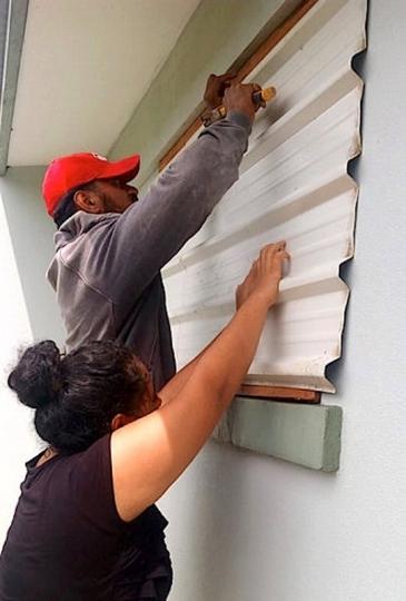 FILE PHOTO: A supplied image shows locals covering windows to office buildings as part of preparations for Cyclone Gita in the Tonga capital of Nuku'alofa, February 12, 2018.  Taniela Hoponoa/CARE Australia/Handout via REUTERS
