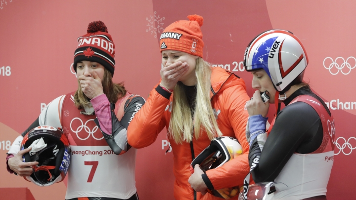 Silver medalist Dajana Eitberger of Germany, center, watches the final sliders with Kimberley McRae of Canada, left and Erin Hamlin of the United States in the finish area after the women's luge final at the 2018 Winter Olympics in Pyeongchang, South Korea, Tuesday, Feb. 13, 2018. (AP Photo/Wong Maye-E)