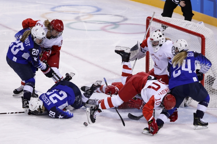 Players collide in front of the goal during the second period of the preliminary round of the women's hockey game between the United States and the team from Russia at the 2018 Winter Olympics in Gangneung, South Korea, Tuesday, Feb. 13, 2018. (AP Photo/Frank Franklin II)