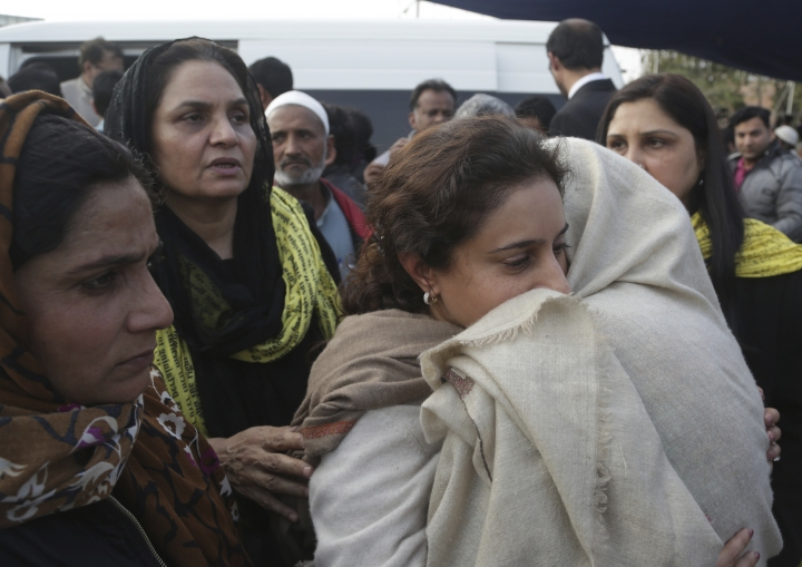 People comfort a family member of prominent Pakistani lawyer Asma Jahangir in Lahore, Pakistan, Tuesday, Feb. 13, 2018. Pakistan has bid farewell to rest one of the country's most prominent human rights activists, Jahangir, who died this week of a heart attack in the eastern city of Lahore. (AP Photo/K.M. Chaudary)