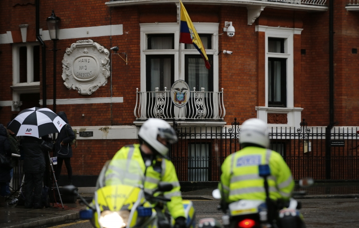 Police motorcyclists briefly stop outside the Ecuadorian embassy in London, Tuesday, Feb. 13, 2018. A British judge is set to decide Tuesday whether to quash or uphold an arrest warrant for WikiLeaks founder Julian Assange, who has spent more than five years evading the law inside Ecuador's London embassy. Assange's lawyers argue that it's no longer in the public interest to arrest him for jumping bail in 2012 and seeking shelter in the embassy to avoid extradition to Sweden, where prosecutors were investigating allegations of sexual assault and rape made by two women. He denied the allegations.(AP Photo/Alastair Grant)