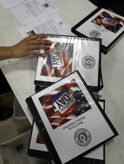 Workers prepare election day kits at the Bear County Election offices, Tuesday, Feb. 13, 2018, in San Antonio. The first primaries of the 2018 elections are less than a month away, but efforts to safeguard the vote against expected Russian interference are lagging. (AP Photo/Eric Gay)