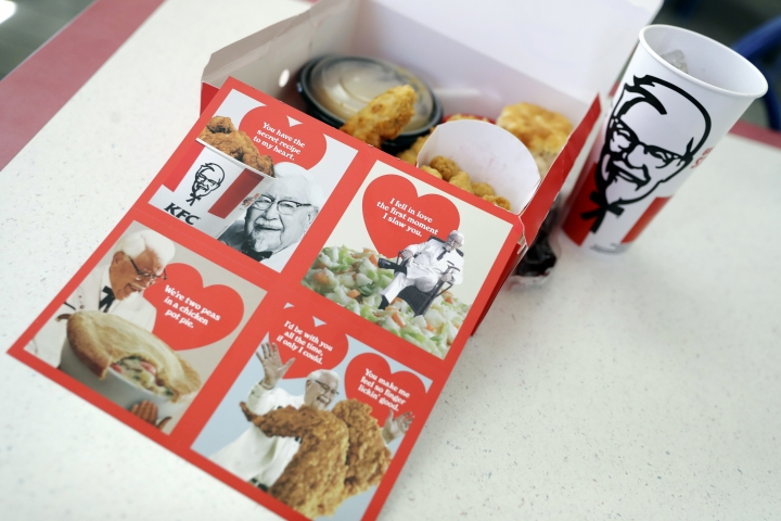 Valentine's Day scratch-and-sniff cards, which give off a fried chicken aroma, sit on a table at a KFC, Tuesday, Feb. 13, 2018, in Santa Clara, Calif. KFC is handing out the cards to diners who buy its $10 Chicken Share meals or a bucket full of Popcorn Nuggets. (AP Photo/Marcio Jose Sanchez)