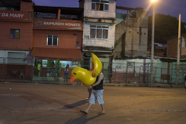 A man walks away with a duck, a costume prop, after Carnival celebrations at the Sambadrome in Rio de Janeiro, Brazil, Tuesday, Feb. 13, 2018. The world-famous two-day parade finished earlier on Tuesday with samba-schools also criticizing the country's politicians amid a series of corruption scandals. (AP Photo/Leo Correa)