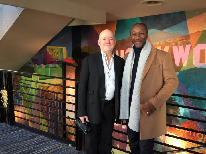 "CORRECTS NAME TO GREG MACGILLIVRAY - Filmmaker Greg MacGillivray, left, poses with singer-songwriter Aloe Blacc at a Manhattan preview of the new IMAX movie ""America's Musical Journey,"" Tuesday, Feb. 13, 2018, in New York. The film is a project of Brand USA, the agency that markets U.S. tourism. In the movie, Blacc visits cities like Memphis and Detroit, soaking up local music styles and heritage as he works on a new song of his own, ""My Story."" (AP Photo/Beth J. Harpaz)"