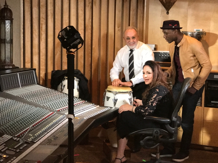 "This undated image taken from video and provided by Brand USA is from the new IMAX movie called ""America's Musical Journey"" and shows Gloria and Emilio Estefan with singer Aloe Blacc, right, adding some Latin beats to Blacc's new song, ""My Story."" The movie premieres Thursday, Feb. 15, 2018, and was produced by Brand USA, the agency that markets the U.S. to the rest of the world, along with MacGillivray Freeman Films. The movie follows Blacc as he travels around the U.S., learning about the musical heritage and genres of music associated with various cities. (Brand USA via AP)"