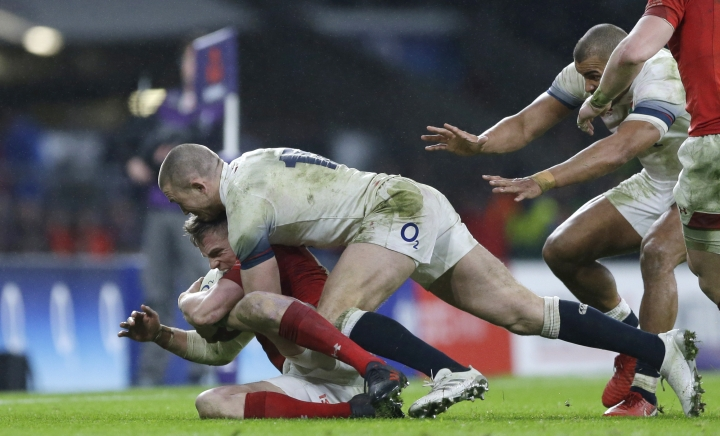 England's Mike Brown, top, pushes Wales' Gareth Anscombe into touch during the Six Nations international rugby union match at Twickenham stadium in London, Saturday, Feb. 10, 2018. (AP Photo/Alastair Grant)