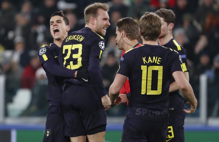 Tottenham's Christian Eriksen, 2nd left, celebrates with teammate Erik Lamela and Harry Kane, right, after scoring his side's second goal during the Champions League, round of 16, first-leg soccer match between Juventus and Tottenham Hotspurs, at the Allianz Stadium in Turin, Italy, Tuesday, Feb. 13, 2018. (AP Photo/Antonio Calanni)