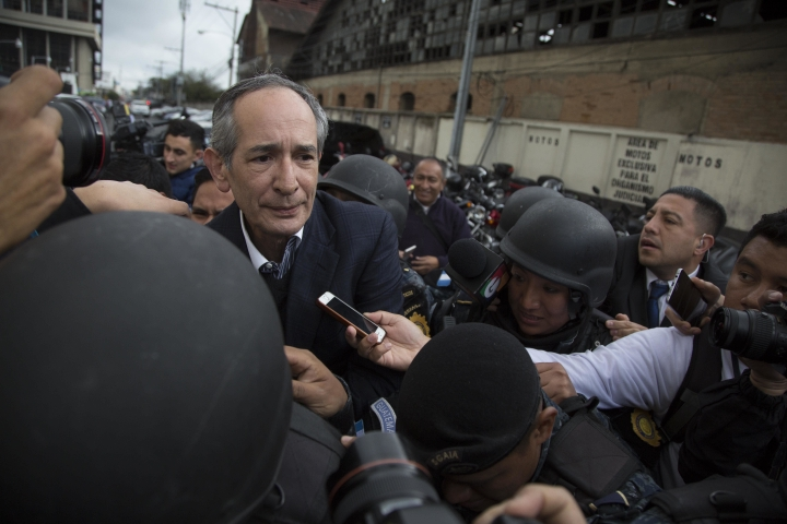 Former Guatemalan President Alvaro Colom, left, is escorted by police to a courtroom in Guatemala City, Tuesday, Feb. 13, 2018. Colom, who governed from 2008 to 2012, has been detained in a corruption case according to special prosecutor Juan Francisco Sandoval. (AP Photo/Luis Soto)