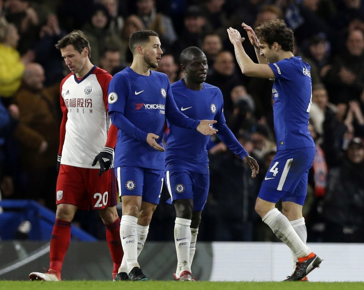 Chelsea's Eden Hazard, second left, celebrates with teammate Cesc Fabregas after he scored his side's third goal of the game during the English Premier League soccer match between Chelsea and West Bromwich Albion at Stamford Bridge stadium in London, Monday, Feb. 12, 2018. (AP Photo/Alastair Grant)