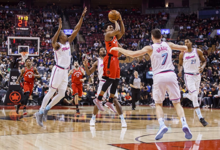 Toronto Raptors' Kyle Lowry puts up a shot against Miami Heat, left to right, Josh Richardson, Goran Dragic, and Hassan Whiteside during the first half of an NBA basketball game, Tuesday, Feb. 13, 2018, in Toronto. (Mark Blinch/The Canadian Press via AP)