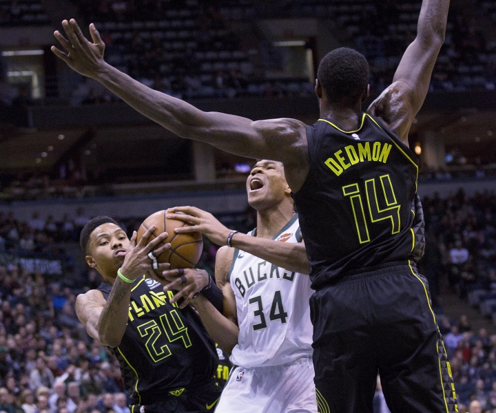 Milwaukee Bucks forward Giannis Antetokounmpo, center, is defended by Atlanta Hawks guard Kent Bazemore, left, and Dewayne Dedmon, right, during the first half of an NBA basketball game Tuesday, Feb. 13, 2018, in Milwaukee. (AP Photo/Darren Hauck)