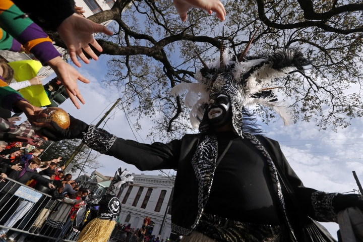 A member of the Crew of Zulu hands out prized painted coconuts as their parade rolls on Mardi Gras day in New Orleans, Tuesday, Feb. 13, 2018. (AP Photo/Gerald Herbert)