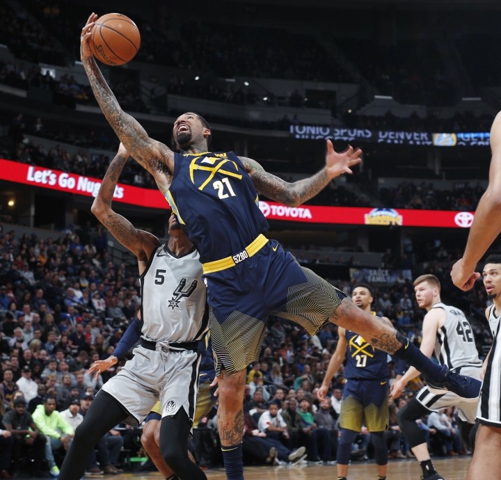 Denver Nuggets forward Wilson Chandler, front, reaches over San Antonio Spurs guard Dejounte Murray for the ball during the first half of an NBA basketball game Tuesday, Feb. 13, 2018, in Denver. (AP Photo/David Zalubowski)