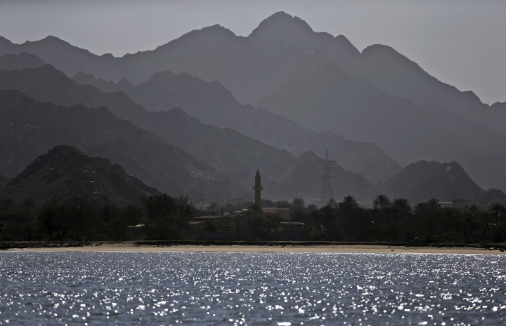 In this Jan. 23, 2018 photo, a mosque's minaret and the Shumayliyah Mountains are seen from Dibba Bay on the Arabian Sea, in Dibba, United Arab Emirates. The waters of the Persian Gulf have long been home to pearl oysters. Now, off these shores in Fujairah, an emirate with a coastline that juts out into the Gulf of Oman, a new type of oyster is thriving -- the edible kind. (AP Photo/Kamran Jebreili)