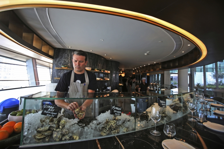 In this Jan. 24, 2018 photo, Carl Maunder, executive chef at the Maine Oyster Bar & Grill at Dubai Opera prepares an oyster dish, in Dubai, United Arab Emirates. The waters of the Persian Gulf have long been home to pearl oysters. Now, off the shores of the Fujairah, an emirate with a coastline that juts out into the Gulf of Oman, a new type of oyster is thriving -- the edible kind. (AP Photo/Kamran Jebreili)