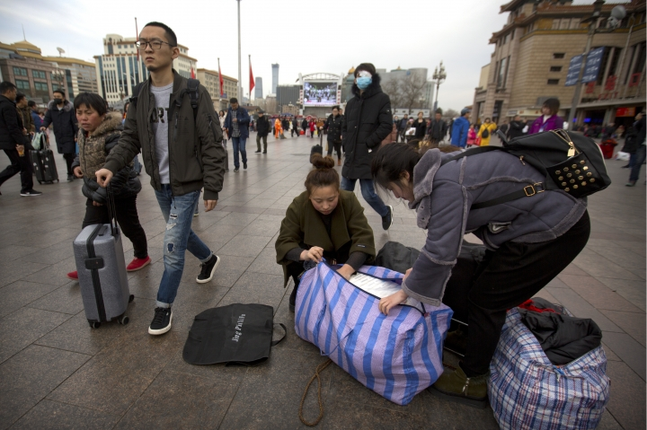 Women unpack their luggage outside of the Beijing Railway Station in Beijing, Wednesday, Feb. 14, 2018. Millions in China were boarding trains, planes and automobiles Wednesday as the Lunar New Year travel rush, the world's largest seasonal human migration, reached its climax. (AP Photo/Mark Schiefelbein)