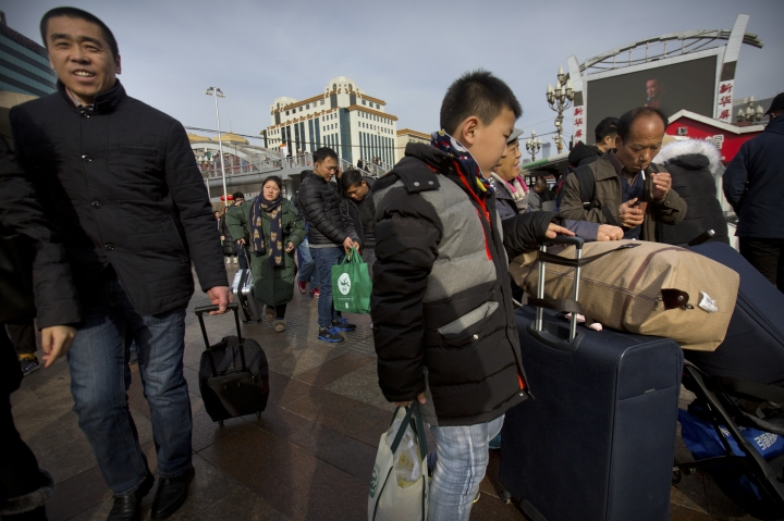 Travelers walk outside of the Beijing Railway Station in Beijing, Wednesday, Feb. 14, 2018. Millions in China were boarding trains, planes and automobiles Wednesday as the Lunar New Year travel rush, the world's largest seasonal human migration, reached its climax. (AP Photo/Mark Schiefelbein)
