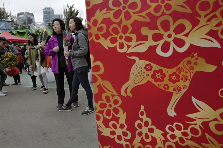 People buy flowers at a New Year market in Hong Kong's Victoria Park, Wednesday, Feb. 14, 2018. Chinese will celebrate the Lunar New Year on Feb. 16 this year which marks the Year of the Dog in the Chinese zodiac. (AP Photo/Vincent Yu)