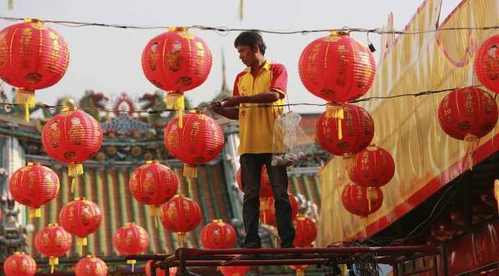 A Thai worker decorates lanterns for celebrations of Chinese New Year at the Leng Nuei Yee Chinese temple in Bangkok, Thailand, Wednesday, Feb. 14, 2018. Chinese New Year falls on Feb. 16 this year, marking the start of the Year of the Dog. (AP Photo/Sakchai Lalit)