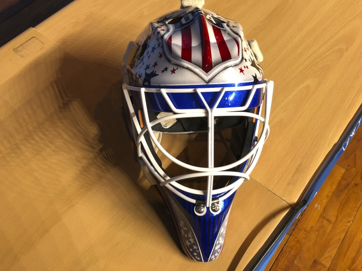 In this Monday, Feb. 12, 2018 photo, the mask of United States men's hockey goaltender Brandon Maxwell is displayed at the 2018 Winter Olympics, in Pyeongchang, South Korea. The mask is a mix of the U.S. logo and stars and stripes. Maxwell wanted to make his Olympic mask a tribute to former New York Rangers goalie Mike Richter but was blocked by the International Olympic Committee. (AP Photo/Stephen Whyno)