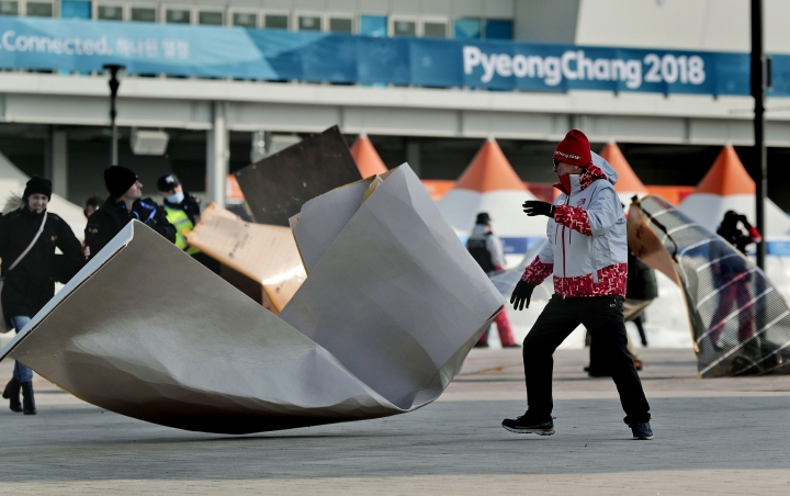 A volunteer chases down solar film backing that blew off the Coca-Cola building inside Gangneung Olympic Park at the 2018 Winter Olympics in Gangneung, South Korea, Wednesday, Feb. 14, 2018. Spectators were advised to either stay inside competition venues or leave the park because of high winds. (AP Photo/Julie Jacobson)
