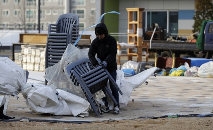 A volunteer gathers plastic chairs blown over by fierce wind at the Gangneung Media Village in Gangneung, South Korea, Wednesday, Feb. 14, 2018. (AP Photo/Petr David Josek)