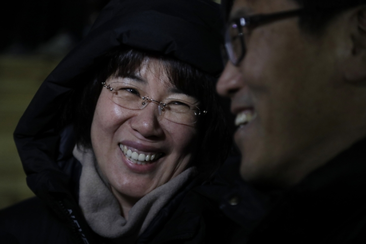 In a photo taken Monday, Feb. 12, 2018, Heo Saeng-gum, left, and her husband Kim Woo Il, right, react during an interview before entering the Kwandong Hockey Center to watch their daughter Kim Selin play for the Koreas during a women's hockey game against Sweden at the 2018 Winter Olympics in Gangneung, South Korea. Parents of players at Koreas' joint women's hockey team say they are so proud of their daughters for creating history in inter-Korean relations. (AP Photo/Julio Cortez)
