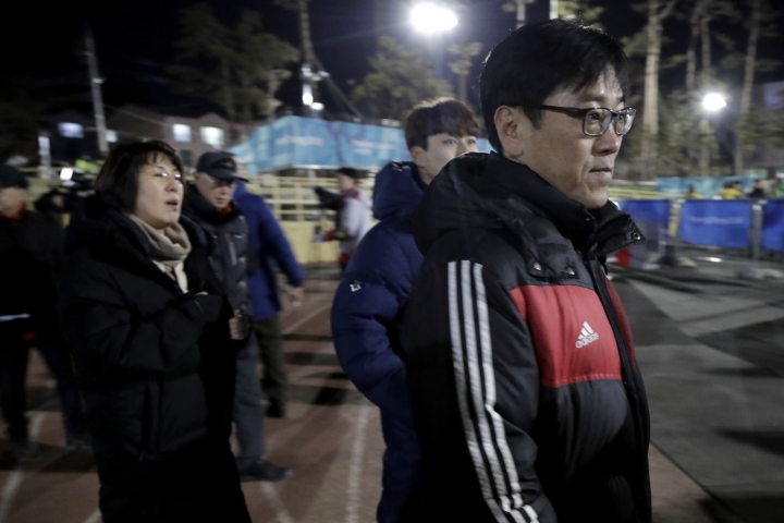 In a photo taken Monday, Feb. 12, 2018, Kim Woo Il, right, walks with his wife Heo Saeng-gum, left, and their son Kim Se Hyung, center, as arrive at the Kwandong Hockey Center to watch their daughter Kim Selin play for the Koreas during a women's hockey game against Sweden at the 2018 Winter Olympics in Gangneung, South Korea. Parents of players at Koreas' joint women's hockey team say they are so proud of their daughters for creating history in inter-Korean relations. (AP Photo/Julio Cortez)