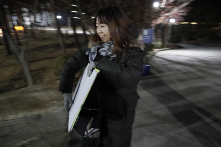 In a photo taken Monday, Feb. 12, 2018, Woo Hee-jun, mother of South Korean player Han Dohee, arrives at the Kwandong Hockey Center to watch her daughter play for the Koreas during a women's hockey game against Sweden at the 2018 Winter Olympics in Gangneung, South Korea. Parents of players at Koreas' joint women's hockey team say they are so proud of their daughters for creating history in inter-Korean relations. (AP Photo/Julio Cortez)