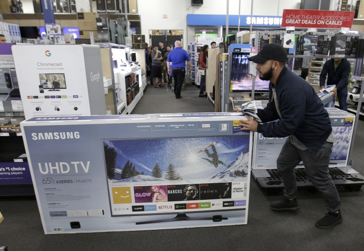 FILE - In this Nov. 23, 2017, file photo, Jesus Reyes pushes a television down an aisle as he shops at a Black Friday sale at a Best Buy store in Overland Park, Kan. On Wednesday, Feb. 14, 2018, the Commerce Department releases U.S. retail sales data for January. (AP Photo/Charlie Riedel, File)