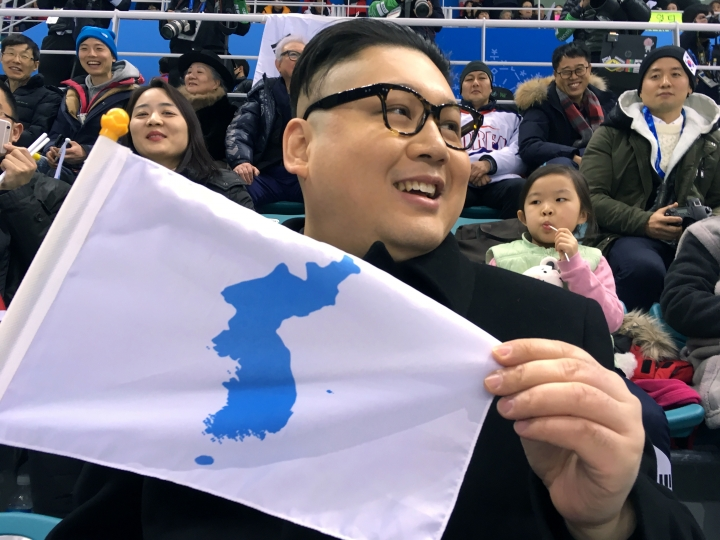 A Kim Jong Un impersonator, calling himself only Howard from Australia, holds a unification flag while attending the Korea-Japan women's ice hockey game at the 2018 Winter Olympics in Pyeongchang, South Korea, Wednesday, Feb. 14, 2018. (AP Photo/Eric Talmadge)