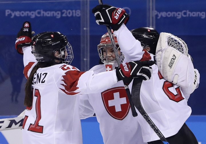 Laura Benz (21), goalie Florence Schelling (41) and Livia Altmann (22), of Switzerland, celebrate after the preliminary round of the women's hockey game Sweden at the 2018 Winter Olympics in Gangneung, South Korea, Wednesday, Feb. 14, 2018. Switzerland won 2-1. (AP Photo/Matt Slocum)