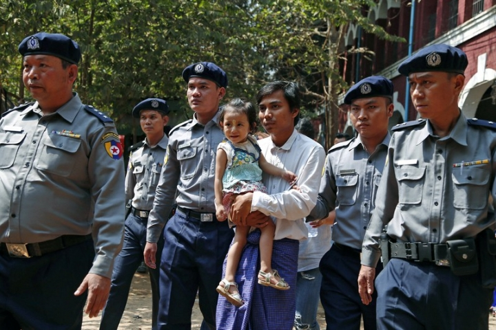 Detained Reuters journalist Kyaw Soe Oo is escorted by police as he holds his daughter while arriving for a court hearing after lunch break in Yangon, Myanmar February 14, 2018. REUTERS/Stringer