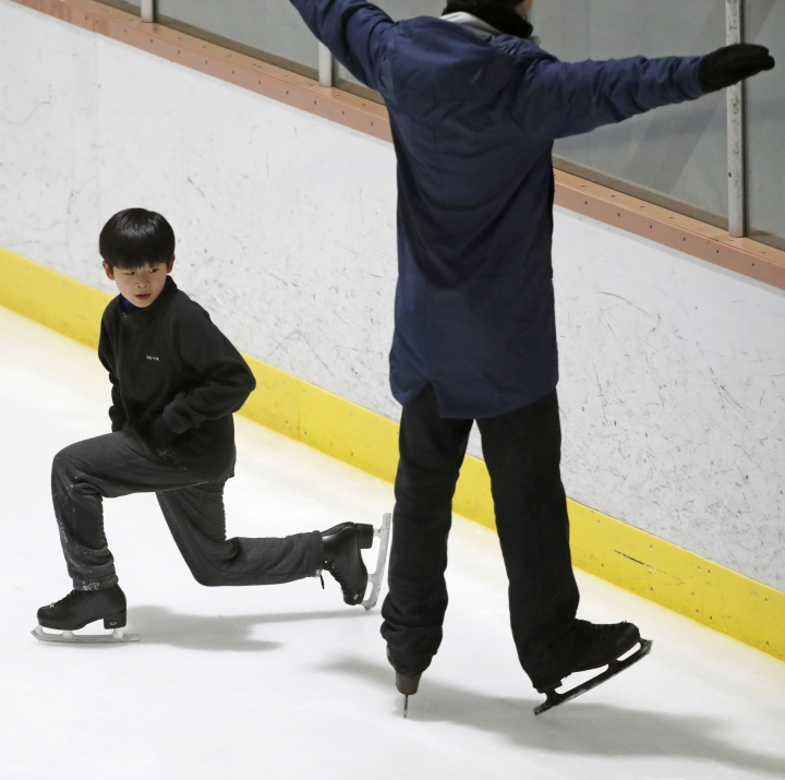 Keita Horiko, left, the 10-year-old U.S. Figure Skating juvenile boys champion, watches his coach, Kevin Coppola, during a training session Thursday, Feb. 8, 2018, at the Ice House in Hackensack, N.J. Asian-Americans are taking center ice during the figure skating competition at the Pyeongchang Olympics, where half of the U.S. figure skating team is Asian-American. (AP Photo/Kathy Willens)