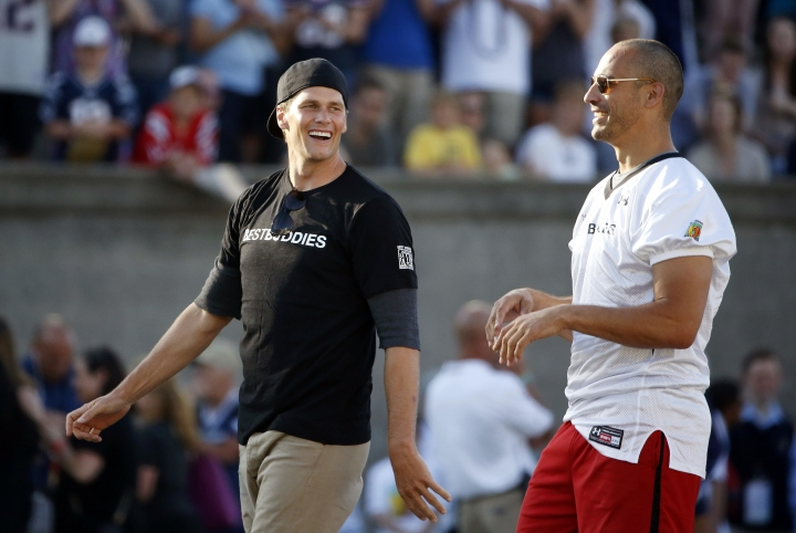 "FILE - In this May 29, 2015 file photo, New England Patriots quarterback Tom Brady, left, walks with former Patriots tight end Christian Fauria during the Best Buddies Challenge charity football game in Boston. Boston sports radio station WEEI announced Wednesday, Feb. 14, 2018, that live programs will halt from 6 a.m. to 6 p.m. on Friday while employees receive ""sensitivity training."" It comes a week after talk show host Fauria impersonated Brady's agent Don Yee on air. Yee is of Chinese descent but was born in Sacramento, Calif. Fauria was suspended for five days and has since apologized. (AP Photo/Michael Dwyer, File)"