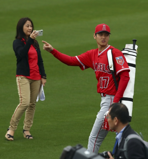 Los Angeles Angels' Shohei Ohtani gestures to fans as he takes the field during a spring training baseball practice on Wednesday, Feb. 14, 2018, in Tempe, Ariz. (AP Photo/Ben Margot)